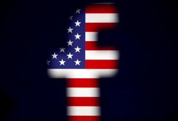 A 3D-printed Facebook logo is displayed in front of a U.S. flag in this illustration